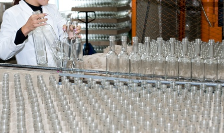 production of alcohol drinks - an operator puts empty bottles on conveyor