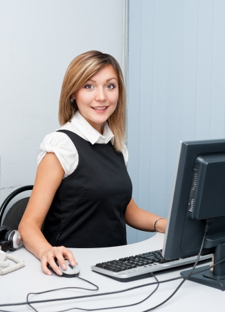 young caucasian woman sitting in front of a computer looks into camera and smiles