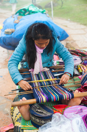 DALAT, VIETNAM - JULY 30, 2014: An unidentified local young woman weaves by hand at Lang Biang mountain. Its height is 1,900m and one can walk there by a 3 hours hike, or can ride by a jeep.