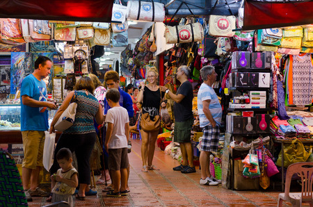 SIEM REAP, CAMBODIA - JUNE 21, 2014: Unidentified tourists shop at the night market of Siem Reap. The city serves as a gateway to the world famous Angkor temples and is a major tourist hub.