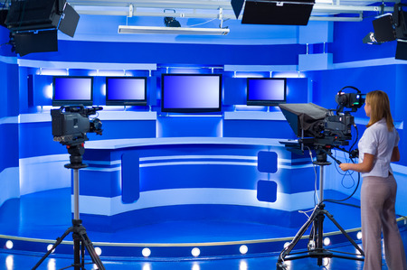 woman cameraman works at empty blue TV studio