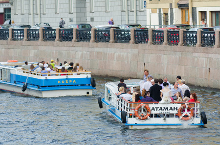 ST PETERSBURG - JUNE 30, 2011: Four river buses wait for mooring at the Moyka Embankment after tour. River tours are very popular as there are about 100 rivers and channels in the city.