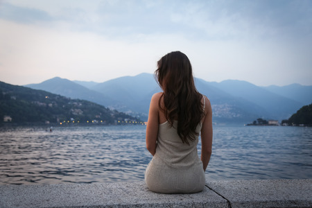 Photo pour The young woman looking at the beautiful view at the lake - image libre de droit