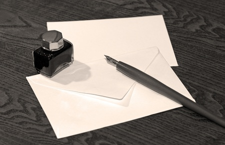 Old wooden ink pen on wooden table with blank letter.