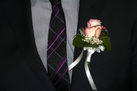 Closeup of the groom's suit with rose.