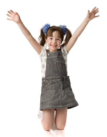 little girl stands on knees and holds hands up, isolated on white