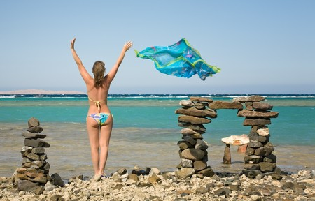 young woman standing on sea beach with silk shawl