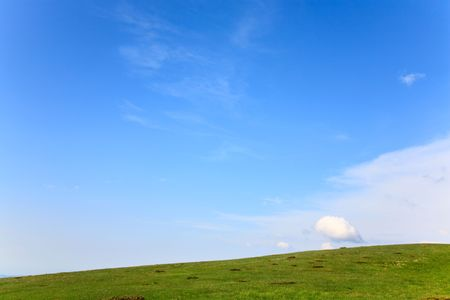 green grass covered summer mountainside and cloudy sky