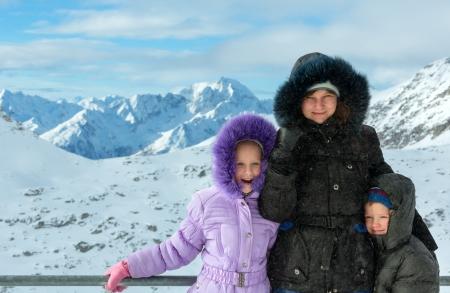 Family on ski station top and morning winter mountain landscape. Ski resort Molltaler Gletscher, Carinthia, Austria.