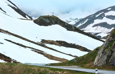 Summer mountain landscape with road, cross and bench (Oberalp Pass, Switzerland)