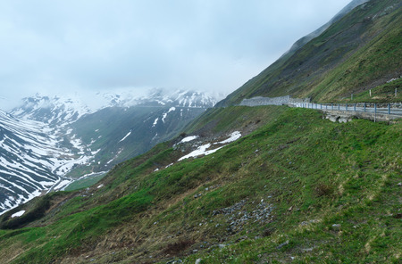 Summer cloudy mountain landscape with road (Oberalp Pass, Switzerland)