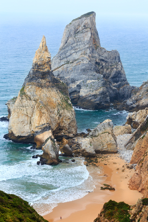 Atlantic ocean coast (granite boulders and sea cliffs) in cloudy weather. View from Cape Roca (Cabo da Roca), Portugal. Man on beach is unrecognizable.