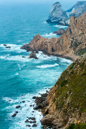 Atlantic ocean coast (granite boulders and sea cliffs) in cloudy weather. View from Cape Roca (Cabo da Roca), Portugal.