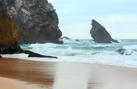 Atlantic ocean coast view (granite boulders, sea cliffs and beach) in cloudy stormy weather near Cabo da Roca, Portugal.