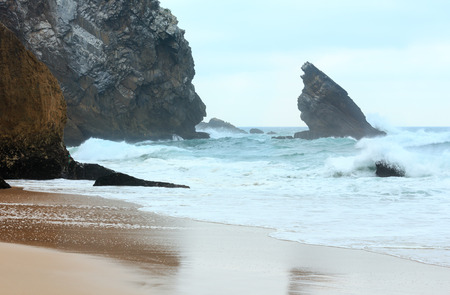 Atlantic ocean waves breaking on granite boulders near beach in stormy weather (Cabo da Roca, Portugal).