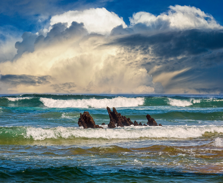 Photo pour Sea surf waves and small rocks in center. Seascape view from beach. - image libre de droit