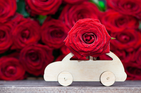 Foto de Concept Valentine day, love, machine transports a flower on the background of red roses. Stylish love concept, space for text. - Imagen libre de derechos