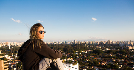 Teenager sitting on top of a building admiring the skyline of So Paulo, Brazil.