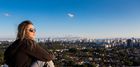 Teenager sitting on top of a building admiring the skyline of S? ? o Paulo, Brazil.