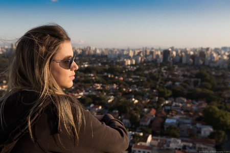 Teenager sitting on top of a building admiring the skyline of  Brazil.