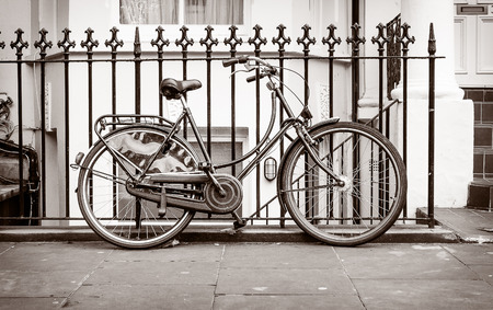 Female bike leaning against a vintage grille, photographed in black and white in Notting Hill, London