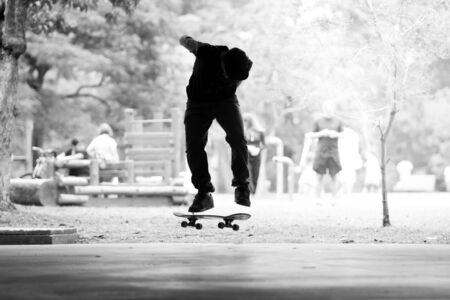 Boy practicing street skateboard, freestyle in black and white.