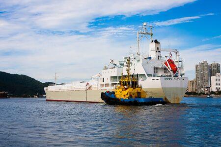 Photo pour Tugboat guiding a ship at the entrance of the Port of Santos, Brazil. - image libre de droit