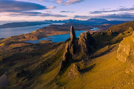 Photo pour An aerial view from the Storr of the Old Man of Storr with the Black Cuillin mountains in the distance. The sun has only just risen above the horizon on a beautiful May morning on the Isle of Skye, Scotland, UK. - image libre de droit