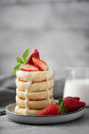 Photo for cottage cheese pancakes with fresh strawberries, mint and milk on a gray plate - Royalty Free Image