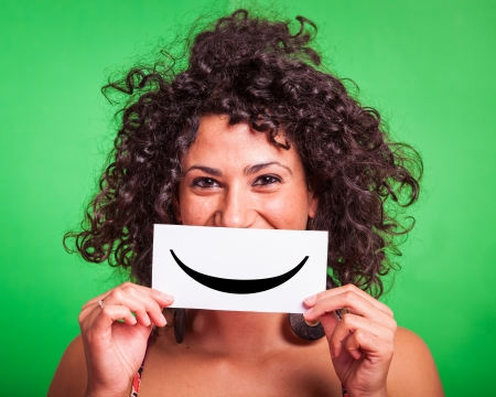 Photo for Young Woman with Smiley Emoticon on Green Background - Royalty Free Image