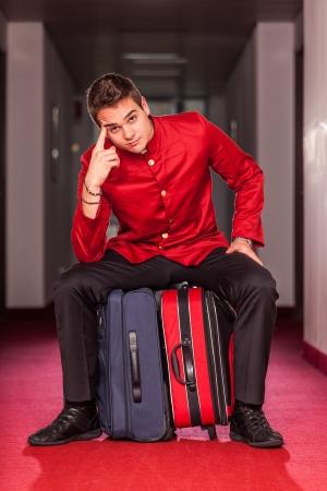Photo pour Tired Bellboy with Luggages - image libre de droit