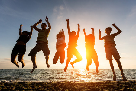 Photo pour Multiracial Group of People Jumping at Beach, Backlight - image libre de droit
