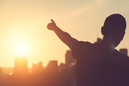 Successful Man aiming at Sunset