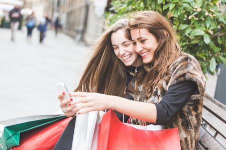 Photo pour Happy Women with Smart Phone and Shopping Bags - image libre de droit