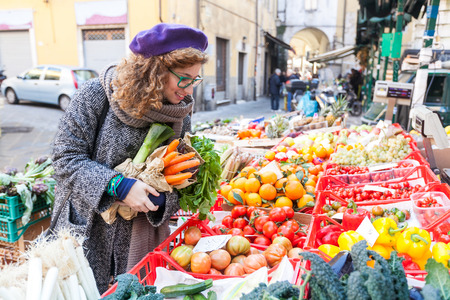 Young Woman Buying Vegetables at Local Marketの写真素材