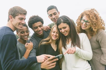 Photo pour Multiethnic Group of Friends Looking at Mobile Phone - image libre de droit
