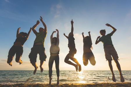 Foto de Multiracial group of people jumping at beach. Backlight shot. Happiness, success, friendship and community concepts. - Imagen libre de derechos