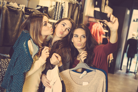 Three women taking a selfie while shopping in a clothing store. They are happy and smiling at camera. Shopping concept, also related to social media addiction.