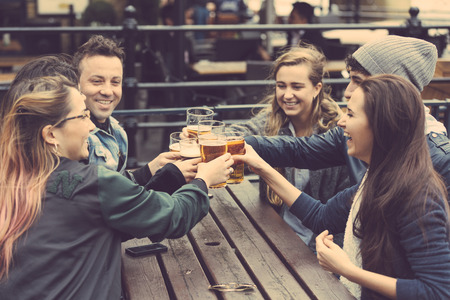 Photo pour Group of friends enjoying a beer at pub in London, toasting and laughing. They are four girls and two boys in their twenties. - image libre de droit