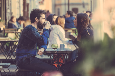 Foto de Hipster couple drinking coffee in Stockholm old town. They're sitting face to face. The man is wearing a blue sweater and the woman a striped shirt with black leather jacket. See-through shot. - Imagen libre de derechos