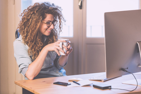 Photo for Young woman working at home or in a small office, vintage hipster clothing, curly hair. Cup of tea or coffee on the desk with some technological devices. - Royalty Free Image