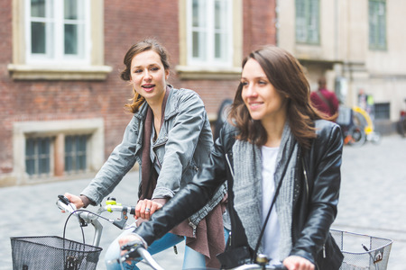 Two women going by bike in Copenhagen. They are in their twenties and they are wearing smart casual clothes. Bicycles are a typical mode of transport in Denmark.