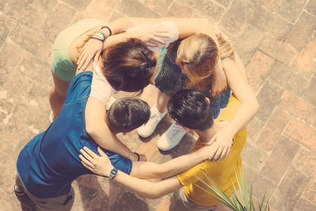 Foto de Group of teenagers embraced in circle, aerial view. They are two girls and two boys, looking each other - Imagen libre de derechos