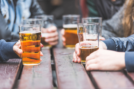 Photo for Hands holding glasses with beer on a table at pub in London. A group of friends is enjoying beer time in the city, close up on the glasses. - Royalty Free Image