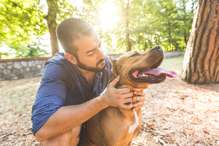 Portrait of a man with dog at park. He is looking at his dog standing with open mouth. The main subject is the dog, the man is standing behind it.
