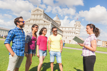 Photo pour Group of tourists in Pisa, Italy. A group of friends is listening to a guide talking about a famous monument. They are two women and two men wearing summer clothes. They are a multicultural group on holidays. - image libre de droit