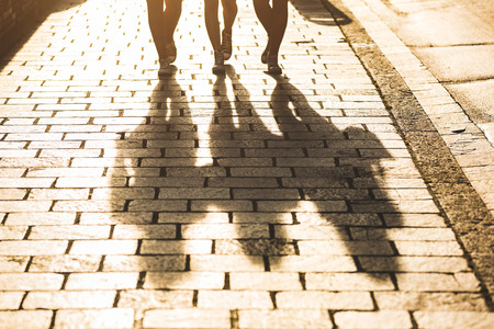 Photo pour Shadows of three girls walking on a sidewalk in the city at sunset. Focus on the shadows, and harsh backlight with flares. Lifestyle concept with a different point of view. - image libre de droit