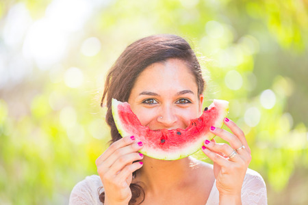 Photo pour Beautiful young woman showing a slice of watermelon as a smile. She is caucasian, she wear a white dress and she has a braid on the shoulder. Summer and lifestyle concepts. - image libre de droit