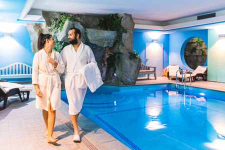 Photo pour Couple in relax at therme with swimming pool. Man and woman wearing batrobe enjoying time at spa. Leisure and luxury relax concepts - image libre de droit