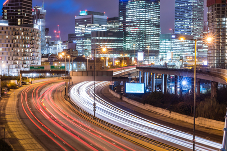 Photo for City night view with skyscrapers and traffic light trails. London urban scene in Canary Wharf with busy road and lights of financial district on background. Travel and architecture concepts - Royalty Free Image